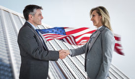 Composite image of pleased businessman shaking the hand of content businesswoman Royalty Free Stock Photo