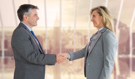 Composite image of pleased businessman shaking the hand of content businesswoman Stock Images