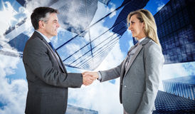 Composite image of pleased businessman shaking the hand of content businesswoman Stock Image
