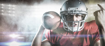 Composite image of portrait of american football player gesturing while holding ball Stock Photo