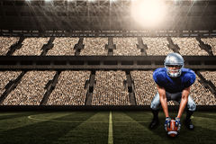 Composite image of portrait of american football player placing ball with 3d. Portrait of American football player placing ball against football stadium with Stock Photos