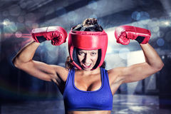 Composite image of portrait of angry female boxer flexing muscles Stock Photos