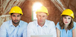 Composite image of portrait of architects wearing hardhats while sitting at table Stock Images