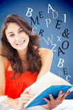 Composite image of portrait of a beautiful student reading a blue book Royalty Free Stock Images