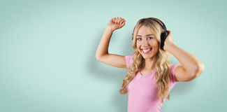 Composite image of portrait of a beautiful woman dancing with headphones Stock Photos