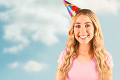Composite image of portrait of a beautiful woman with party hat. Portrait of a beautiful woman with party hat  against cloudy sky Stock Image