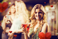 Composite image of portrait of blonde woman drinking cocktail Royalty Free Stock Photography