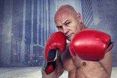 Composite image of portrait of boxer with fighting stance. Portrait of boxer with fighting stance against urban projection on wall stock image