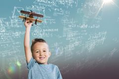Composite image of portrait of boy holding wooden toy airplane. Portrait of boy holding wooden toy airplane against blue sky Stock Image