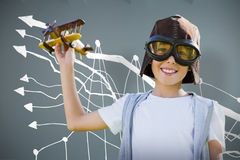 Composite image of portrait of boy wearing flying goggles with toy. Portrait of boy wearing flying goggles with toy against room with wooden floor Stock Image
