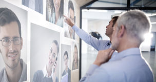 Composite image of portrait of business people. Portrait of business people against businessman showing something on board to colleague stock photography