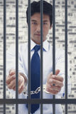 Composite image of portrait of a businessman with handcuffs Stock Photo