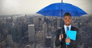 Composite image of portrait of businessman holding blue umbrella and file. Portrait of businessman holding blue umbrella and file against new york city view Stock Images