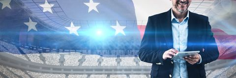 Composite image of portrait of businessman using tablet computer. Portrait of businessman using tablet computer against close-up of an american flag stock images