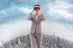 Composite image of portrait of a businesswoman looking through binoculars Royalty Free Stock Image