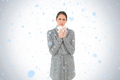 Composite image of portrait of a casual young woman suffering from cold Royalty Free Stock Photography
