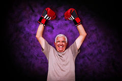 Composite image of portrait of a cheerful senior boxer. Portrait of a cheerful senior boxer against dark background Stock Photo