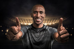 Composite image of portrait of confident athlete smiling and showing thumbs up Royalty Free Stock Photos