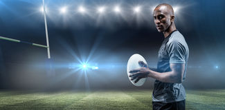 Composite image of portrait of confident athlete standing with rugby ball. Portrait of confident athlete standing with rugby ball against rugby stadium Royalty Free Stock Image