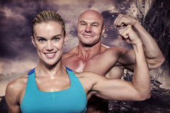 Composite image of portrait of confident cheerful man and woman flexing muscles royalty free stock image