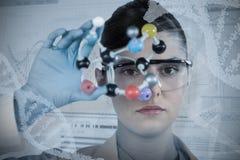 Composite image of portrait of confident female scientist holding molecular model Stock Images