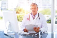 Composite image of portrait of confident male doctor sitting at computer desk. Portrait of confident male doctor sitting at computer desk against breast cancer Royalty Free Stock Image