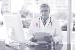 Composite image of portrait of confident male doctor sitting at computer desk. Portrait of confident male doctor sitting at computer desk against breast cancer Stock Image