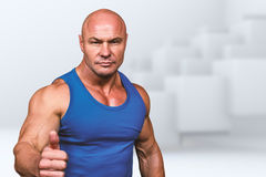 Composite image of portrait of confident muscular man showing thumbs up Royalty Free Stock Image