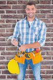 Composite image of portrait of confident repairman holding hammer Stock Photo