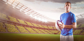 Composite image of portrait of confident rugby player holding ball 3D Stock Images
