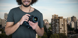 Composite image of portrait of confident smiling male photographer holding camera. Portrait of confident smiling male photographer holding camera against trees Stock Images