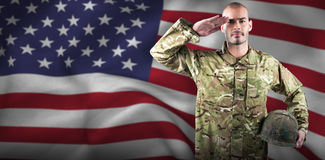 Composite image of portrait of confident soldier holding helmet while saluting Royalty Free Stock Photos