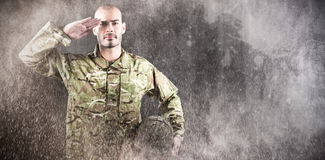 Composite image of portrait of confident soldier holding helmet while saluting Stock Images