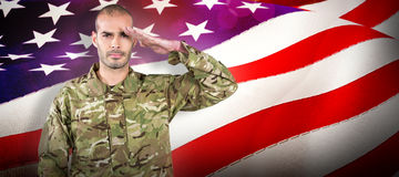 Composite image of portrait of confident soldier saluting. Portrait of confident soldier saluting against waving flag of america Stock Photography
