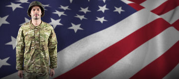 Composite image of portrait of confident soldier standing. Portrait of confident soldier standing against close up of the us flag Royalty Free Stock Image