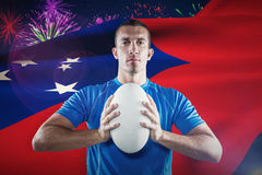 Composite image of portrait of confident sports player in blue jersey holding ball Royalty Free Stock Photos