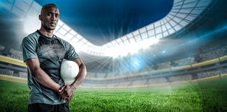 Composite image of portrait of confident sportsman with rugby ball Royalty Free Stock Photography