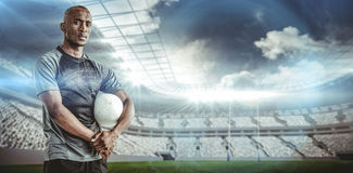 Composite image of portrait of confident sportsman with rugby ball Royalty Free Stock Photo