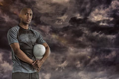 Composite image of portrait of confident sportsman with rugby ball Stock Photography
