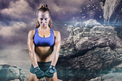 Composite image of portrait of confident woman. Portrait of confident woman against rock crashing down from cliff Stock Photo
