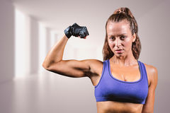 Composite image of portrait of confident woman flexing muscles. Portrait of confident woman flexing muscles against bright hall with windows Royalty Free Stock Photography