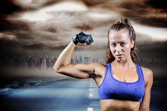 Composite image of portrait of confident woman flexing muscles. Portrait of confident woman flexing muscles against stormy sky with tornado over road Stock Images