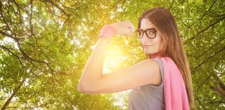 Composite image of portrait of confident woman in superhero costume. Portrait of confident woman in superhero costume against green leaves Royalty Free Stock Photography