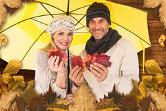 Composite image of portrait of couple holding autumn leaves while standing under yellow umbrella Stock Photography