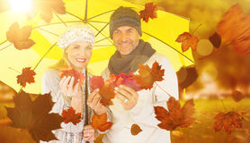 Composite image of portrait of couple holding autumn leaves while standing under yellow umbrella Royalty Free Stock Image