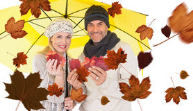 Composite image of portrait of couple holding autumn leaves while standing under yellow umbrella Royalty Free Stock Photography
