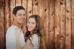 Composite image of portrait of couple hugging. Portrait of couple hugging against wooden planks Stock Images