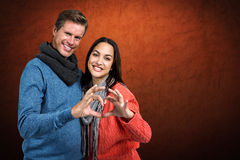 Composite image of portrait of couple making heart shape with hands. Portrait of couple making heart shape with hands against shades of brown Royalty Free Stock Photos