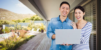 Composite image of portrait of couple using laptop Stock Photography