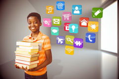Composite image of portrait of cute boy carrying books in library. Portrait of cute boy carrying books in library against computing application icons Royalty Free Stock Photography